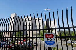 The Federal Detention Center where Blanca Orantes-Lopez is held 3,000 miles away from her child is seen behind a fence as a jet flies overhead, June 19, 2018, in SeaTac, Wash. The woman from El Salvador sits in the federal prison south of Seattle, ha...