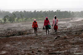 Residents walk in the rain at the Solai farm after their dam burst its walls, overrunning nearby homes, in Solai town near Nakuru, Kenya, May 10, 2018.