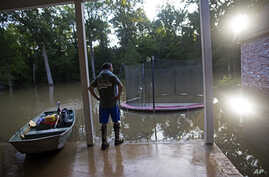 David Key looks at the back yard of his flooded home in Prairieville, La., Aug. 16, 2016. Key, an insurance adjuster, fled his home as the flood water was rising.