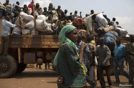 FILE - A woman looks on as people on a truck gather their belongings during a road repatriation to Chad in the capital  Bangui January 22, 2014. Central African Republic's new interim president said on Tuesday she would hold talks with armed groups i