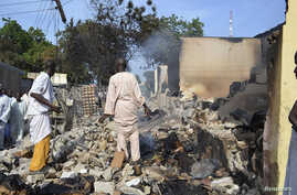 Residents watch as two men walk amidst rubble after Boko Haram militants raided the town of Benisheik, west of Borno State capital Maiduguri September 19, 2013.