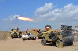 Iraqi government forces and allied militias fire weaponry from a position in the northern part of Diyala province, bordering Salaheddin province, as they take part in an assault to retake the city of Tikrit from jihadists of the Islamic State (IS) gr