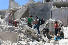 People walk on the rubble of a site hit by a barrel bomb in the rebel held area of Old Aleppo, Syria July 11, 2016.