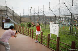 A woman poses for photographs in front of a barbed-wire fence near the demilitarized zone separating the two Koreas in Paju, South Korea, July 14, 2017.