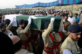 Pakistani troops carry the casket, wrapped in national flag, of provincial candidate Siraj Raisani, who was killed in the Friday's suicide bombing in Mastung, during a funeral prayer in Quetta, Pakistan, July 14, 2018.