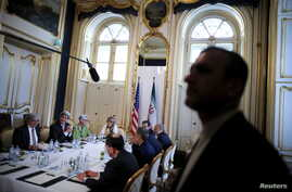 An Iranian security guard stands as U.S. Secretary of State John Kerry (2nd R) meets with the Iranian delegation including Iranian Foreign Minister Mohammad Javad Zarif at a hotel where the Iran nuclear talks meetings are being held in Vienna, Austri