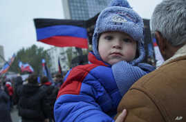 FILE - A man holds a child during celebration of the Flag Day at the Lenin's square, Donetsk  eastern Ukraine.