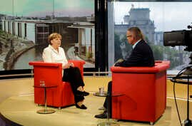 German Chancellor Angela Merkel (L) is seen prior to an interview at the studios of German public broadcaster ARD in Berlin, Germany, July 19, 2015.