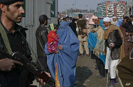 A policeman looks on as passengers wait to cross the Pakistan-Afghanistan border on foot in the northwest town of Torkham, November 27, 2011.
