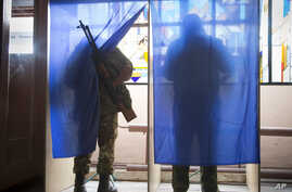Pro-Russian rebels fill their ballots in voting cabins at a polling station set up inside a rebel military base during rebel elections in the city of Donetsk, eastern Ukraine Sunday, Nov. 2, 2014. The pro-Russian rebels are holding the elections that