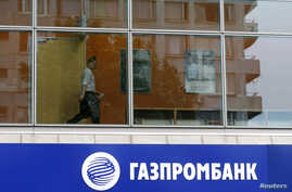 FILE - A person is seen through a window above a Gazprombank branch in Moscow July 17, 2014.