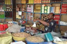 A Sudanese trader weighs produce at his stall in Rubkona Market in Unity state, South Sudan on March 14, 2013. (VOA/Bonifacio Taban)