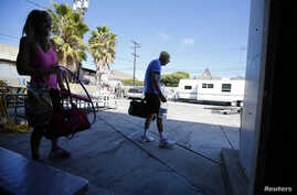 FILE - Parkinson's patient Ron Addison (R) makes his way home after working out with trainer Anne Adams following their twice-weekly Rock Steady Boxing class in Costa Mesa, California.