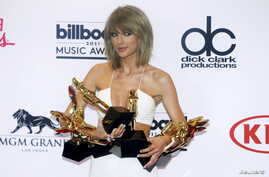 """Singer Taylor Swift poses backstage with her awards for Top Artist, Billboard Chart Achievement Award, Top Female Artist, Top Hot 100 Artist, Top Digital Songs Artist, Top Streaming Song (Video) for """"Shake it Off"""" and Top Billboard 200 Album for """"198"""