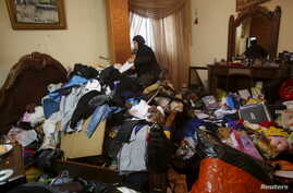 A Palestinian woman inspects the damage to her house, which her family said was searched during an Israeli army raid, following the arrest of a family member by the army in the Askar refugees camp near the West Bank city of Nablus February 23, 2016.