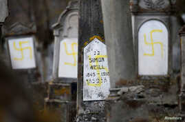 Graves that were desecrated with swastikas are seen at the Jewish cemetery in Quatzenheim, near Strasbourg, France, Feb. 19, 2019.