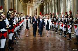 French president Francois Hollande, center, flanked by his companion Valerie Trierweiler, right, Paris' mayor Bertrand Delanoe, second left,and Paris' deputy mayor Anne Hidalgo arrives to deliver a speech as part of a ceremony held at Paris' town hal
