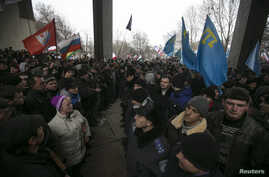 Ukrainian police separate ethnic Russians (L) and Crimean Tatars during rallies near the Crimean parliament building in Simferopol, Feb. 26, 2014.