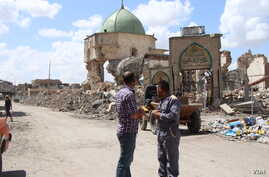 Many areas once controlled by Islamic State militants are still destroyed more than nine months after the battle. Behind these men is the ruins of the al-Nouri Mosque in Mosul, Iraq, May 9, 2018.