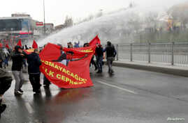 Protesters run from water cannons used by riot police to disperse them during a protest march to commemorate the death of Berkin Elvan, in Istanbul March 11, 2015.