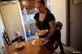 Olga Argyrou prepares to serve lunch to her children at the kitchen of her house at the suburb of Keratsini in Athens, Greece, March 27, 2017.