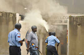 An armed policeman carrying a pistol and tear gas patrols while firemen attempt to put out a fire in the Salvation Army Church after it was set on fire by rioting youths, following Friday Muslim prayers in Mombasa, Kenya, Oct. 4, 2013.