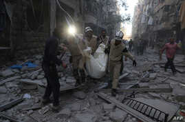Syrian emergency personnel carry a body following an air strike on November 3, 2015, in the rebel-held side of the northern city of Aleppo.