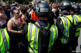 "Police in riot gear block demonstrators at the site where Heather Heyer was killed, on the one year anniversary of 2017 Charlottesville ""Unite the Right"" protests, in Charlottesville, Virginia, Aug. 12, 2018."