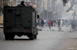 FIILE - Egyptian security forces clash with supporters of ousted president Mohamed Morsi at Nasr City district in Cairo, Nov. 22, 2013.