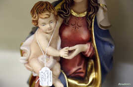 FILE - A statue of Saint Mary and an infant Jesus are displayed for sale in a religious souvenir shop in Rome.