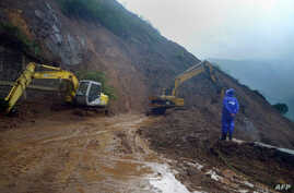 A worker looks at heavy equipment used to clear debris and soil after a mountainside eroded due to heavy rains brought about by Typhoon Goni, along Kennon Road, a main road leading into the Philippine city of Baguio, Aug. 22, 2015.