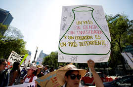 "FILE - A demonstrator holds a placard as she participates in the March for Science rally on Earth Day in Mexico City, Mexico April 22, 2017. The placard reads: ""A country without science, research and education is a country dependent."" Earth Day 2018"