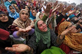 Kashmiri Muslims women react upon seeing a relic believed to be hair from the beard of Prophet Mohammed, being displayed on the Friday following the festival of Eid-e-Milad-ul-Nabi at Hazratbal shrine in Srinagar, India, Jan.1, 2016.
