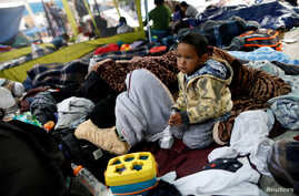 A child traveling with a caravan of migrants from Central America sits at a camp near the San Ysidro checkpoint, after U.S. border authorities allowed the first small group of women and children entry from Mexico overnight, in Tijuana, Mexico, May 1,