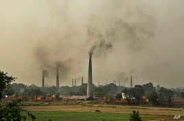 Smoke rises from chimneys of brick kilns on the outskirts of New Delhi, India, June 16, 2015.