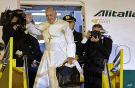 Pope Francis waves good-bye after climbing the stairs to the plane taking him back to Rome, in Asuncion, Paraguay, July 12, 2015.