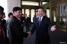 Meng Hongwei (R), Chinese Vice Public Security Minister, shakes hands with Nguyen Quang Dam, the commandant of the Vietnam Coast Guard, in Beijing, China, Aug. 26, 2016.