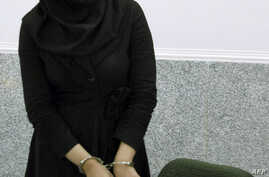 FILE - A picture taken on July 8, 2007 shows Iranian Reyhaneh Jabbari standing handcuffed at police headquarters in Tehran after she was arrested for the murder of a former intelligence official.