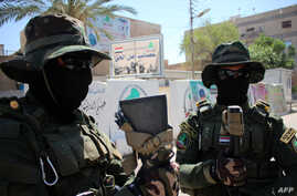 Iraqi fighters of the Shiite militia Asaib Ahl al-Haq (The League of the Righteous) stand guard outside their headquarters on May 18, 2015 in the Iraqi mainly Shiite southern city of Basra, as Shiite militias converged on Ramadi in a bid to recapture