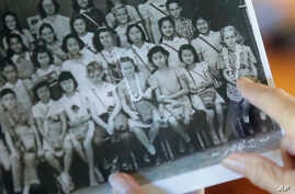 Joan Rodby points to herself in a 1942 photo, in Makawao, Hawaii on Friday, Nov. 18, 2016. After the Pearl Harbor attack, schools required students, including Rodby's childhood friends Emma Veary and Florence Seto,  to carry gas masks with them at al