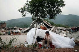 A child sits at a makeshift tent in front of homes destroyed by Saturday's earthquake in Longmen village in Lushan county of southwest China's Sichuan province, April 21, 2013.