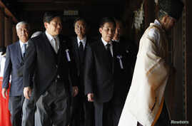 Japan's Land, Infrastructure, Transport and Tourism Minister Yuichiro Hata (2nd L) and other lawmakers are led by a Shinto priest after offering prayers to war dead at Yasukuni Shrine in Tokyo August 15, 2012.