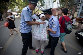 """Chinese police officers attempt to remove a woman protesting with the words """"unjust"""" written on a banner outside the Jinan Intermediate People's Court in Jinan, eastern China's Shandong province, August 21, 2013."""