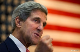 U.S. Secretary of State John Kerry gestures while speaking to U.S. Embassy staff during a break in an extended meeting with Afghan President Hamid Karzai in Kabul October 12, 2013. Karzai extended talks on Saturday as part of a last-ditch effort to n