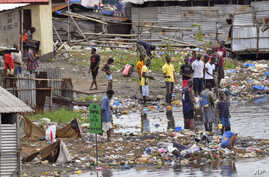 People stand on the polluted shoreline in the West Point neighborhood, an area heavily effected by the Ebola virus, where residents are not being allowed to leave, as government forces clamp down on movement to prevent the spread of Ebola, in Monrovi