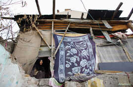 A Syrian refugee woman looks outside from inside her house in Ankara, Nov. 21, 2014.