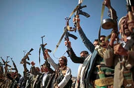FILE - Tribesmen loyal to Houthi rebels hold up their weapons as they attend a gathering to show support for peace talks in Sanaa, Yemen. The U.S. Houseon Feb. 13, 2019, approved a resolution that wouldend U.S. support for the Saudi Arabia-led coal