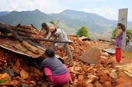 Residents of a destroyed home in Ratomatey scavenge for corn in the rubble.