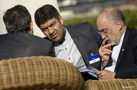 The head of Iranian Atomic Energy Organization Ali Akbar Salehi (R) looks over papers before meetings at the Beau Rivage Palace Hotel March 28, 2015 in Lausanne.