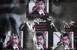 FILE - Torn posters of ousted Egyptian president Mohamed Morsi are seen on a wall at Tahrir Square in Cairo.
